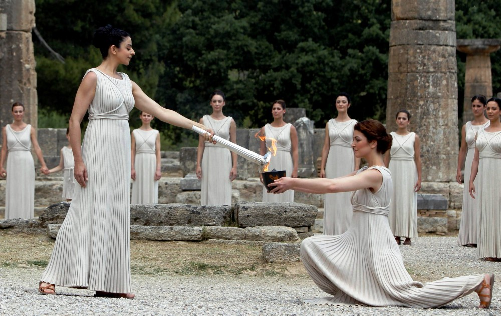 Greek actress Ino Menegaki (R), playing the role of High Priestess, lights the Olympic flame during the torch lighting ceremony of the London 2012 Olympic Games at the site of ancient Olympia in Greece May 10, 2012. REUTERS/John Kolesidis (GREECE - Tags: SPORT OLYMPICS TPX IMAGES OF THE DAY)
